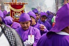 暗示在圣Bartolome在1a Avenida,安提瓜岛,危地马拉的de Becerra队伍的紫色着长袍的人  免版税库存图片