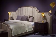 暗色的美丽的现代设计师卧室,与金黄光和落地灯 免版税图库摄影