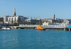暗褐色Laoghaire港口和R n L 我 在威克洛郡海岸的救生艇在爱尔兰在一个镇静春天早晨 免版税库存图片