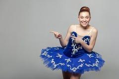 暴牙的兴高采烈的美丽的芭蕾舞女演员妇女画象在蓝色费用 免版税库存图片