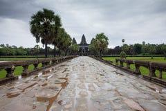 暹粒,柬埔寨- 2014年6月25日, :对吴哥窟寺庙的走道在2014年6月25日,暹粒,柬埔寨的一阴暗天 图库摄影