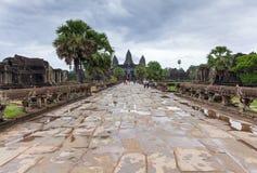 暹粒,柬埔寨- 2014年6月25日, :对吴哥窟寺庙的走道在2014年6月25日,暹粒,柬埔寨的一阴暗天 免版税库存照片