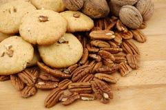 曲奇饼、核桃和山核桃果在一张木纹理桌上 库存图片