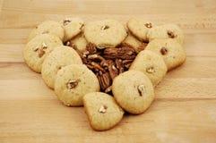 曲奇饼、核桃和山核桃果在一张木纹理桌上 免版税库存照片