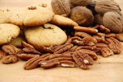 曲奇饼、核桃和山核桃果在一张木纹理桌上 免版税库存图片