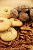 曲奇饼、核桃和山核桃果在一张木纹理桌上 库存照片