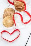 曲奇饼、牛奶瓶在白色木背景和心脏 免版税库存照片