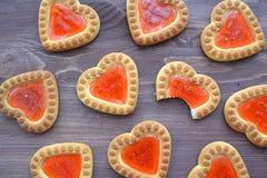 曲奇饼以心脏的形式用红色果酱,纹理背景 爱华伦泰概念 早餐桌 节日晚会,生日 免版税库存图片