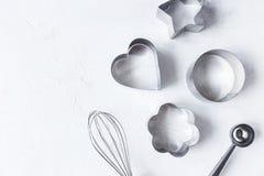 曲奇饼切削刀,在白色厨房用桌上的厨房辅助部件 免版税库存照片