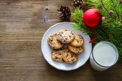 曲奇饼和牛奶圣诞老人的木背景的 库存照片