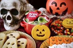 曲奇饼和糖果在一张被装饰的桌上为万圣夜 免版税库存图片