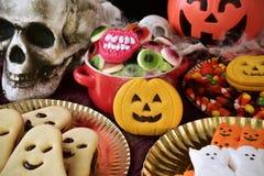 曲奇饼和糖果在一张被装饰的桌上为万圣夜 免版税库存照片