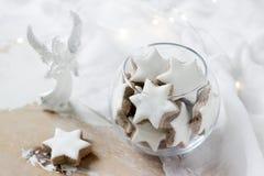 曲奇饼在一个玻璃花瓶的桂香星在用天使和诗歌选的小雕象装饰的白色背景 库存照片