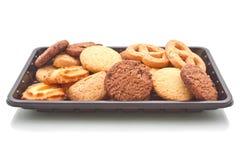 曲奇饼堆在黑塑料盘子的,在白色 免版税库存照片