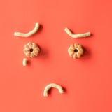 曲奇饼形状的面孔 花曲奇饼在桃红色背景结块 平的位置 免版税库存照片