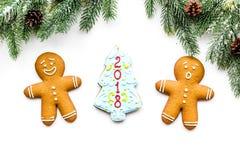 曲奇饼新年 姜饼人和云杉与字法2018在云杉的分支附近在白色背景顶视图 免版税库存照片
