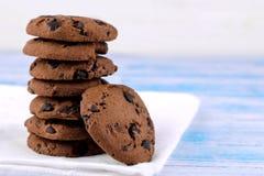曲奇饼用在一块白色餐巾的堆折叠的巧克力在一张蓝色木桌上 bacterias 美味 图库摄影