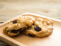 曲奇饼用巧克力和马卡达姆坚果 安置在一块木板材 免版税库存图片
