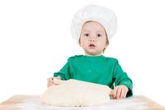 曲奇饼的微笑的小男孩揉的面团,隔绝在白色 免版税库存照片