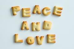 """从曲奇饼的题字在白色背景 文本†""""和平和爱 库存照片"""