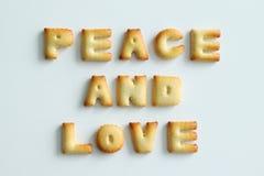 """从曲奇饼的题字在白色背景 文本†""""和平和爱 免版税库存照片"""