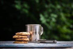 曲奇饼,在户外桌上的旅游金属杯子 免版税库存图片