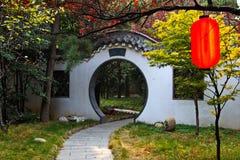 曲拱和红色灯笼在中国庄园里 免版税库存图片