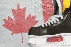 曲棍球冰鞋和加拿大旗子 免版税库存图片