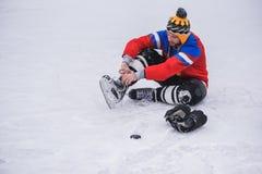 曲棍球运动员坐冰栓鞋带 图库摄影