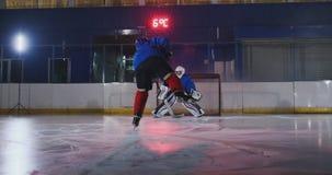 曲棍球运动员展开对对手的目标的一次攻击 在盔甲捉住顽童并且保存比赛 曲棍球 股票视频