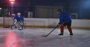 曲棍球运动员展开对对手的目标的一次攻击 在盔甲捉住顽童并且保存比赛 曲棍球 影视素材