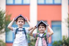 更加年轻的入学年龄、男孩和他的朋友的两个孩子是在绿草的看书 图库摄影