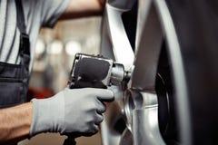 更换在汽车服务的一个轮胎:车修理车间 免版税库存图片