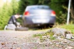 更换新的备用轮胎的人在车以后击中了在countrysi的岩石 免版税库存照片