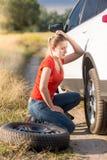 更换有备用一个的哀伤的少妇平车轮胎在领域 免版税库存图片