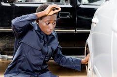 更换汽车的轮胎的少妇技工 免版税图库摄影