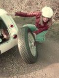 更换运动的轮胎的金发碧眼的女人 库存图片