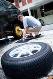 更改他的人轮胎的汽车 免版税库存图片