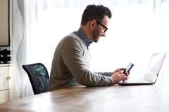 更老的人在家与膝上型计算机和手机一起使用 库存图片