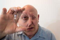 更老的人看通过一个大透镜的,畸变,秃头,脱发症,化疗,癌症,在白色 免版税库存照片