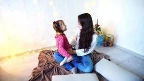 更老的女性姐妹的通信与女孩坐地板在墙壁背景的屋子里与诗歌选和 影视素材