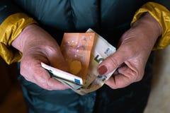 更老的资深妇女拿着欧元钞票-东欧薪金退休金 免版税库存图片