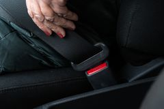 更老的资深妇女紧固在穿绿色和救生服的汽车的一个安全带 免版税库存照片