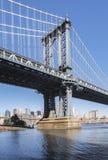 曼哈顿从清早布鲁克林的桥梁塔有蓝天和太阳亮光的 免版税库存照片
