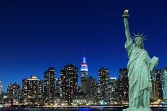 曼哈顿地平线和自由女神象在晚上 免版税库存照片