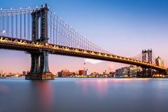曼哈顿桥梁被照亮在黄昏 免版税库存图片
