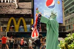 曼哈顿,纽约- 6月, 2016作为自由女神像的生存雕象人表现与美国国旗时常摆正 免版税库存照片
