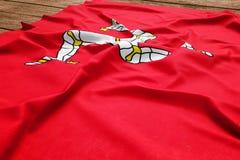 曼岛旗子木书桌背景的 丝绸旗子顶视图 免版税库存照片