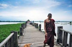 曼德勒,缅甸- 2013年10月9日:走在U Bein桥梁,缅甸的未认出的年轻修士 库存照片