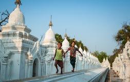 曼德勒, MYANMAR-MAY 1 :男孩新手在Hsinbyume塔寺庙onMAY 1日的前面寺庙2013年在曼德勒,缅甸 库存照片